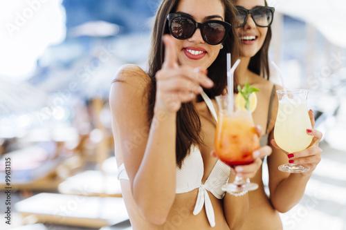 Beautiful women on beach enjoying cocktails Poster