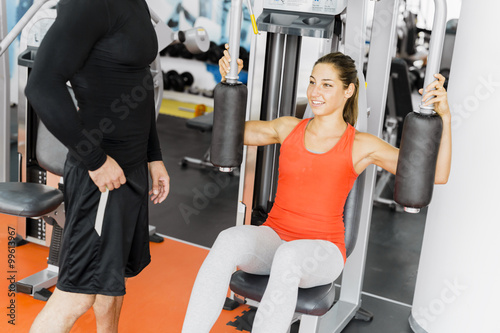 Young male trainer giving instructions to a woman in a gym Canvas Print