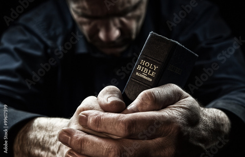 A Man praying holding a Holy Bible. Fototapeta
