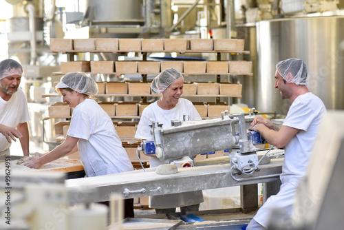 fröhliche Arbeiter bei der Herstellung von Backwaren und Broten in einer Großbäckerei // cheerful workers in the industrial production of bread in a bakery
