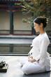 Woman Meditating Outdoors Next To Tea Set