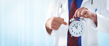 Male Doctor Holding An Alarm Clock