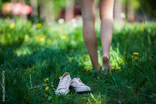 Photo Woman walking barefoot on the grass, pink shoes in focus, shallow DOF