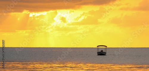 Fotobehang Zwavel geel Golden ocean sunset with a boat silhouette.