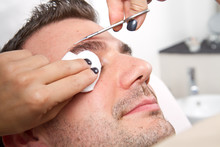 Beautician Plucking A Beautiful Man Eyebrows With Tweezers In A
