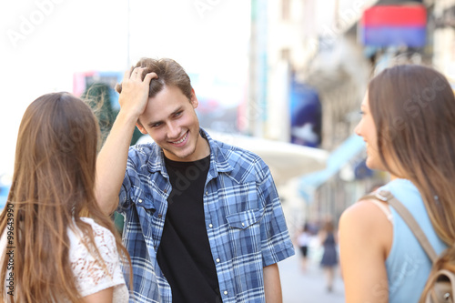 Canvas Print Young man flirting with two girls
