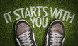 Leinwanddruck Bild - Top View of Sneakers on the grass with the text: It Starts With You