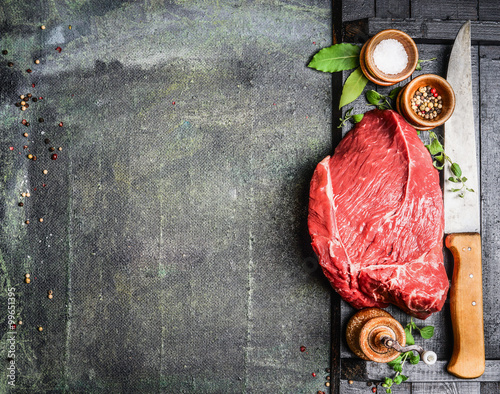 Keuken foto achterwand Vlees Fresh raw meat with herbs,spices and butcher knife on rustic background, top view, place for text. Cooking concept. Horizontal.