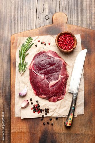 Fotografie, Tablou  Raw ribeye steak on a cutting board, top view