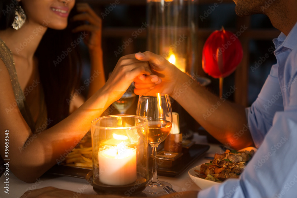Fototapeta Romantic couple holding hands together over candlelight