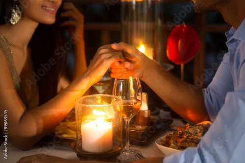 Fotografie, Obraz  Romantic couple holding hands together over candlelight