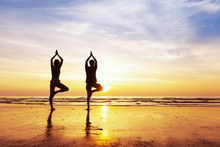 Two People Practicing Yoga Tree Position On The Beach, Sunset