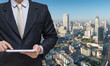 Businessman hold tablet with city background
