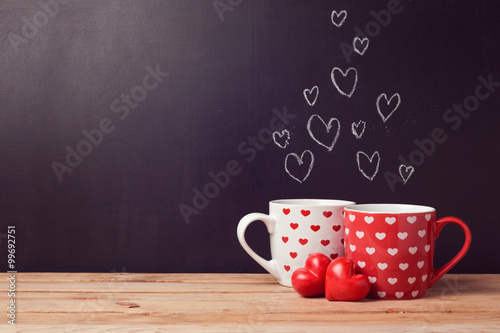 Photo  Valentine's day concept with hearts and cups over chalkboard background