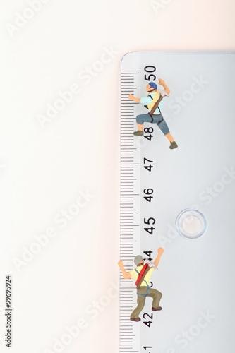 Foto op Plexiglas Alpinisme scalatori in miniatura in arrampicata su un righello in centimetri