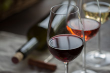 Bottle Of Wine  With Three Wineglasses Of Red, Rose And White Wine On Brown Wood Textured Table Covered With Canvas Towel