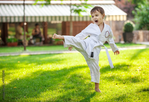 fototapeta na lodówkę Preschool boy practicing karate outdoors