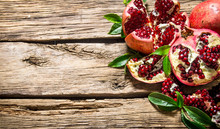 Fresh Pomegranate With Leaves . On Wooden Background.
