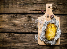 Baked Potatoes In Foil On A Wo...
