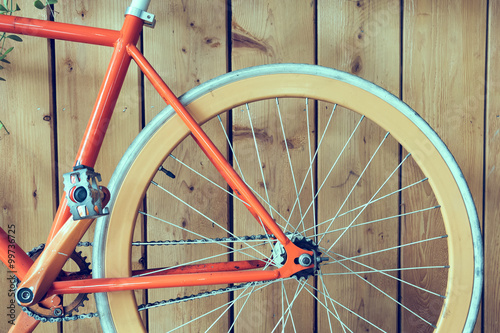 Tuinposter Fiets fixed gear bicycle parked with wood wall, close up image