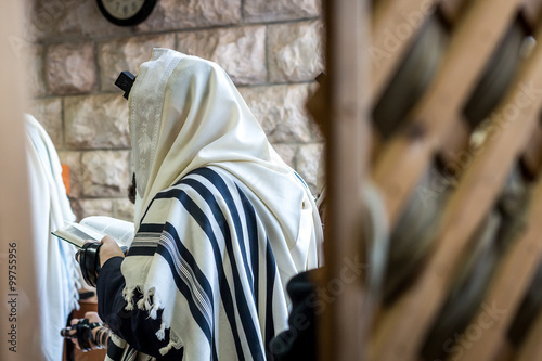 Fototapeta Jewish men praying in a synagogue with Tallit