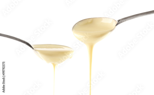 Poster Confiserie Condensed milk pouring from spoons, isolated on white