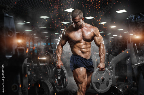 Poster Fitness Muscular athletic bodybuilder fitness model posing after exercises in gym