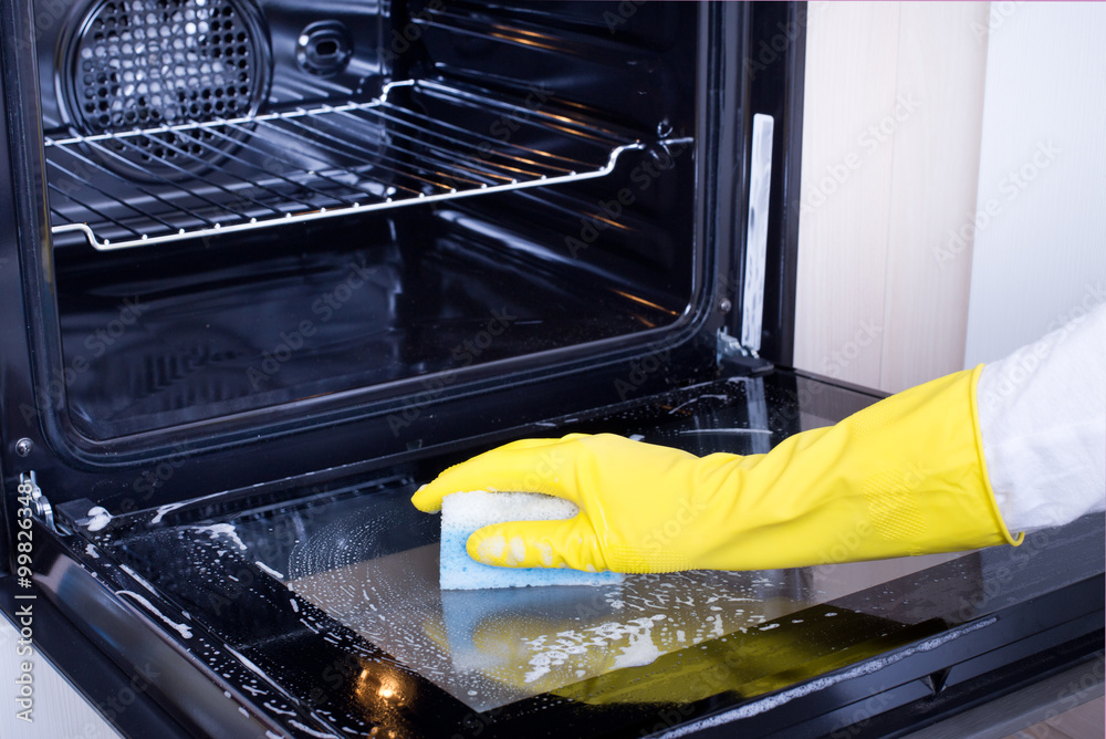 Fototapeta Woman cleaning oven