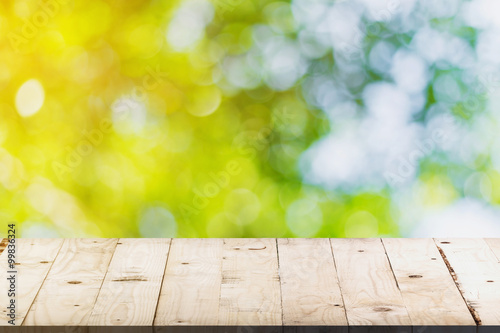 Poster Bois green bokeh and soft light in garden and wood table with space