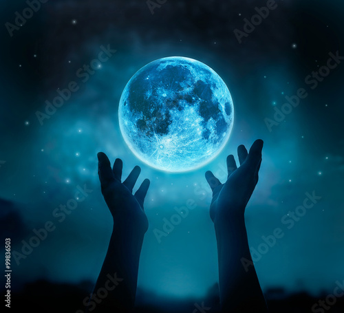 Valokuvatapetti Abstract hands while praying at blue full moon with star in dark background