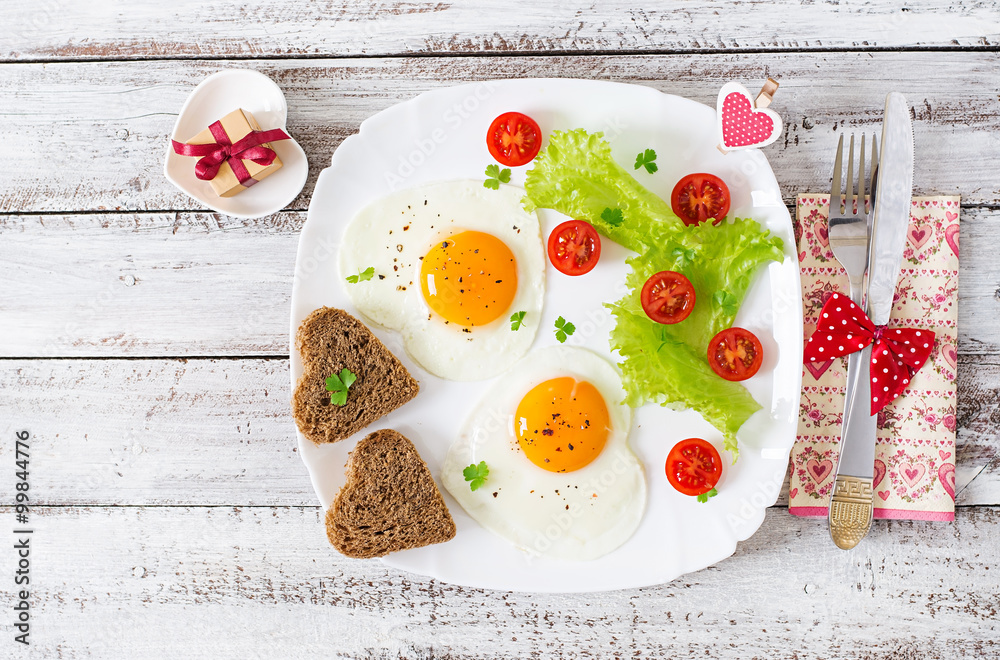 Fototapeta Breakfast on Valentine's Day - fried eggs and bread in the shape of a heart and fresh vegetables. Top view