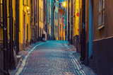 Fototapeta Uliczki - The narrow street of Gamla Stan - historic city old center of Stockholm, at summer night, with lanterns