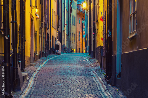 In de dag Stockholm The narrow street of Gamla Stan - historic city old center of Stockholm, at summer night, with lanterns