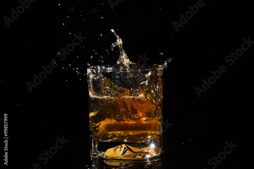 Foto op Canvas Alcohol Quality glass of whiskey with splashes from falling slice of lemon on black background.