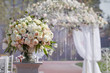canvas print picture - Beautiful bouquet of roses in a vase on a background of a wedding arch. Beautiful set up for the wedding ceremony.