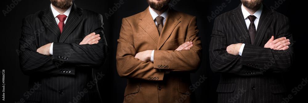 Fototapeta Group of three men in suits black background
