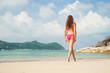 Rare view of sexy, hot woman wearing pink alluring bikini on the beach in Thailand over background with an island.
