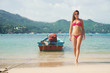 Attractive, hot, young lady with slim body walking out from the sea in Thailand over background with boat and island.