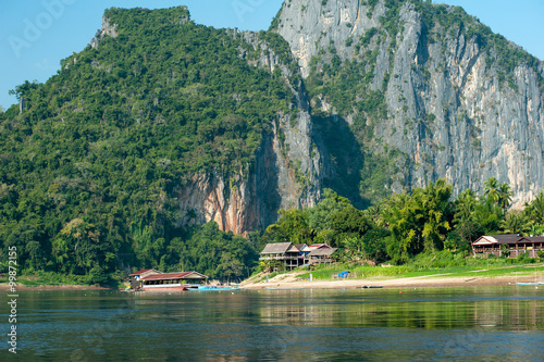 Foto  Traditional village on foot of big mountain in Laos countryside