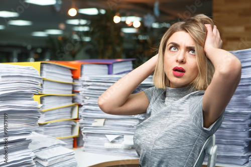 Fotografía  Office businesswoman at her desk full of documents, showing an overwhelmed expre