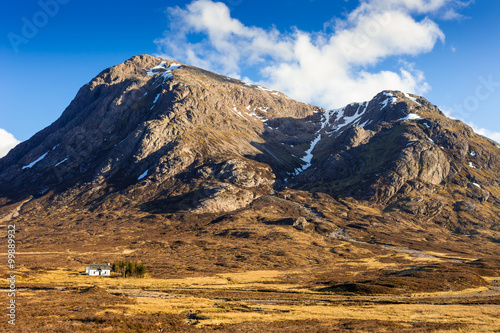 Photo  Detail shot about the Glencoe with a lovely white cottage on a sunny spring day