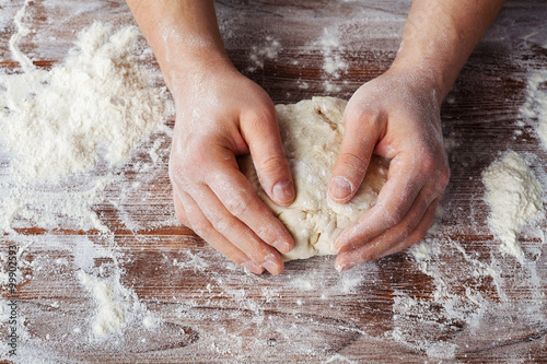 Fotografie, Obraz  Baker prepares the dough on a wooden table, male hands knead the dough with flou