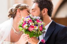 Bridal Couple Giving Kiss In Church At Wedding
