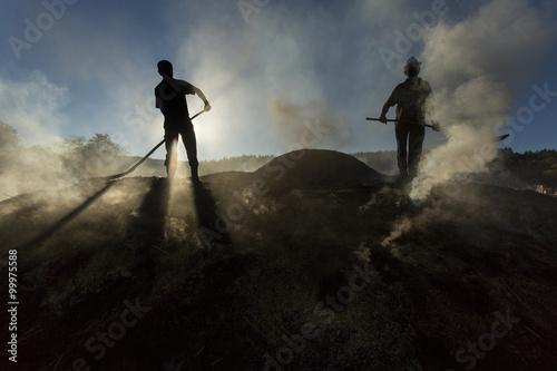 Stampa su Tela Silhouette of coal man working at sunset in smoke