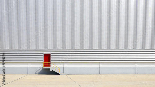 Staande foto Industrial geb. the sheet metal factory wall with the red door entrance