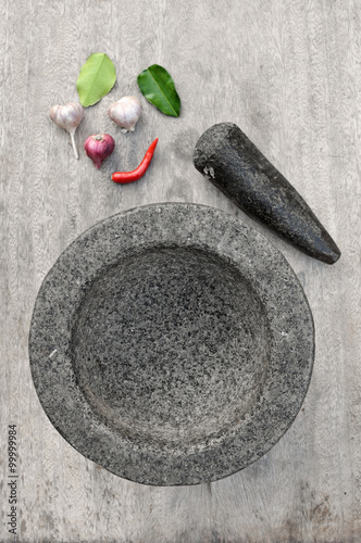 Stone mortar with many kind of herbs in kitchen