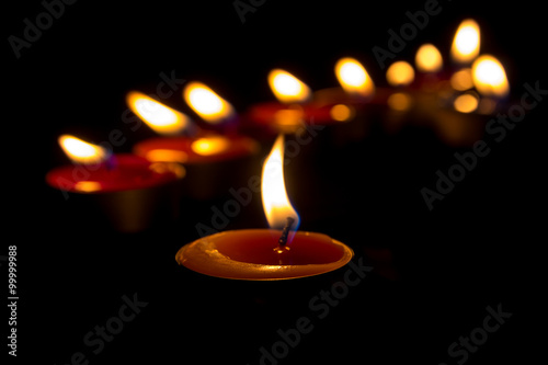 Stampa su Tela Burning candles on a dark background with warm light