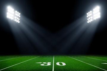 Football field illuminated by stadium lights