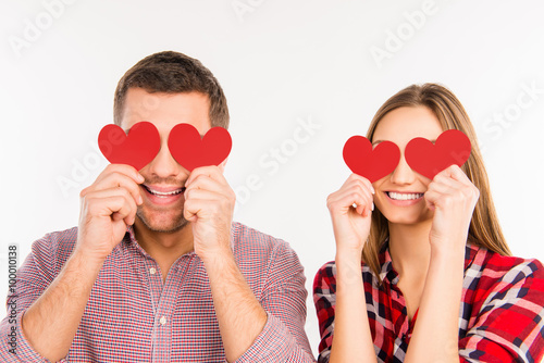 Close up photo of happy couple in love hiding eyes behind  paper Poster