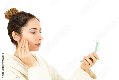 Obraz na plátně  Woman applying make up by looking to her mirror